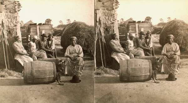 Adults Seated, Facing Camera, Child Playing in Barrel in Foreground, Plantation Setting