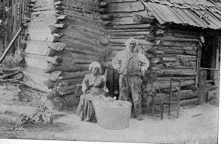 Former Slaves Standing in Front of their Cabin