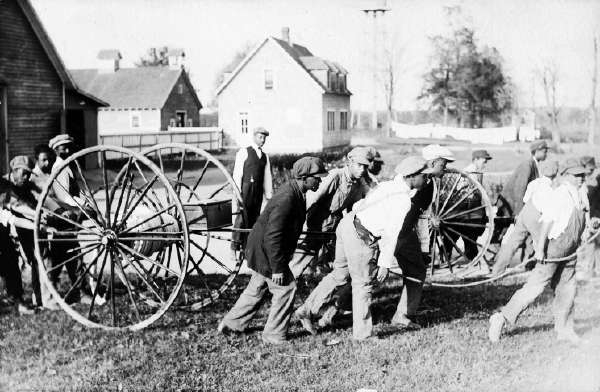 Postcard of Young Men Pushing and Pulling Carts in a Yard at the Howard Orphanage and Industrial School
