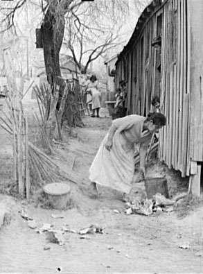 Mexican Woman Cleaning Her Backyard. San Antonio, Texas