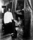Porter Handing Young Woman A Glass Of Water In Railroad Sleeping Car