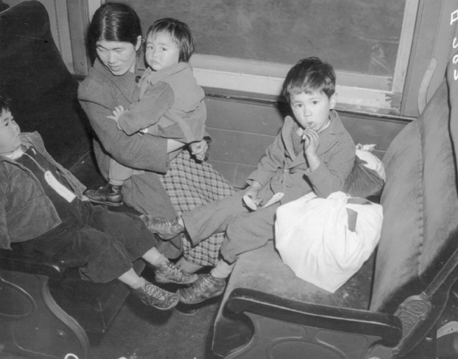 Mother and three children on train from Los Angeles to Manzanar